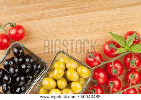 Olives, tomatoes and basil on cutting board with copyspace