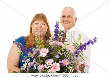 Husband giving his wife a huge bouquet of flowers.  Isolated on white.
