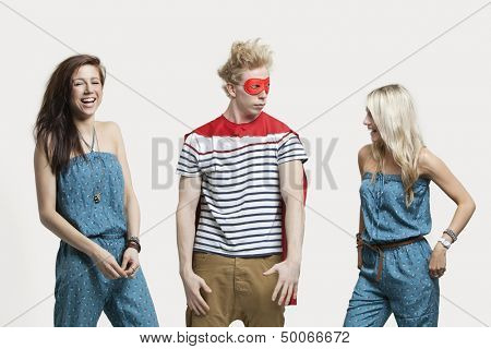 Young man in superhero costume standing with happy female friends in matching jump suits against gray background