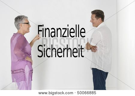 Couple discussing financial security against white wall with German text
