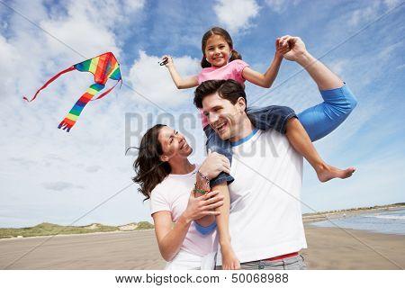 Family Having Fun Flying Kite On Beach Holiday