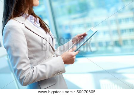 Side-view of a female office worker holding a digital tablet