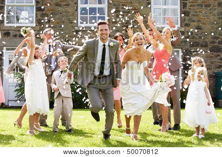 Gasten gooien Confetti Over bruid en bruidegom