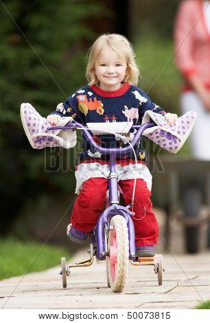 Girl Riding Bike Along Garden Path