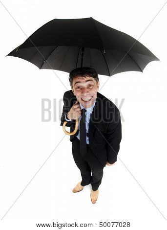 Obsequious businessman sheltering under an umbrella looking up at the camera from underneath with a cheesy insincere smile, high angle humorous portrait isolated on white