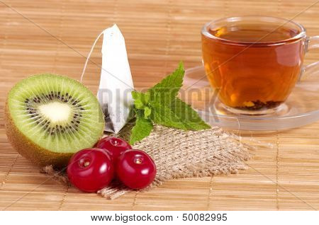 Tasty tea (tea package) in cup with fruits