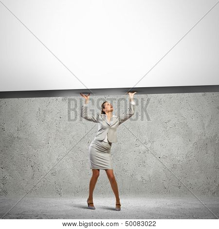 Businesswoman holding blank banner above head. Place for text