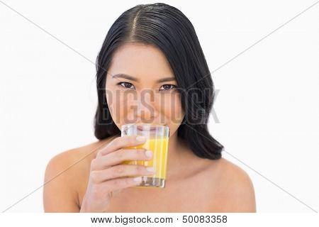 Sensual nude model drinking orange juice on white background