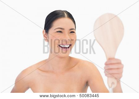 Laughing dark haired young model looking at her reflection on white background