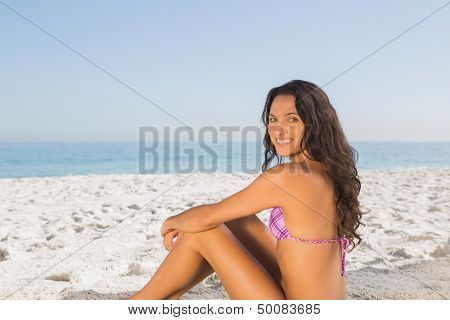 Smiling sexy brown haired woman in pink bikini sitting on the beach