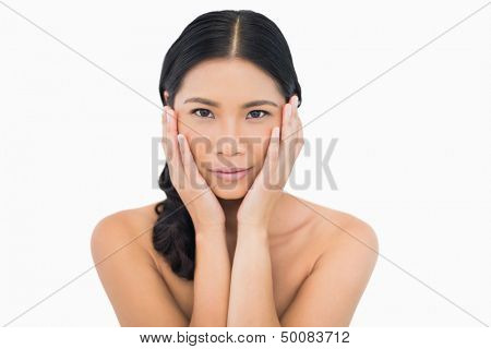 Sensual dark haired model touching her face on white background