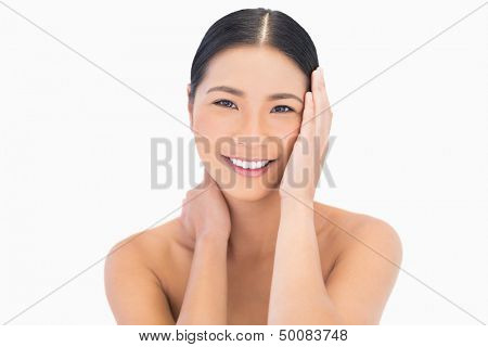 Smiling natural dark haired model touching her face on white background