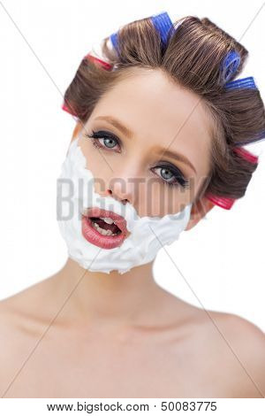 Model in hair curlers with shaving foam in close up on white background