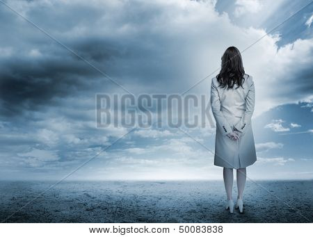 Businesswoman looking out to horizon in a stormy desert landscape