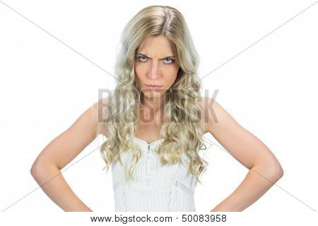 Frowning seductive model in white dress hands on hips on white background