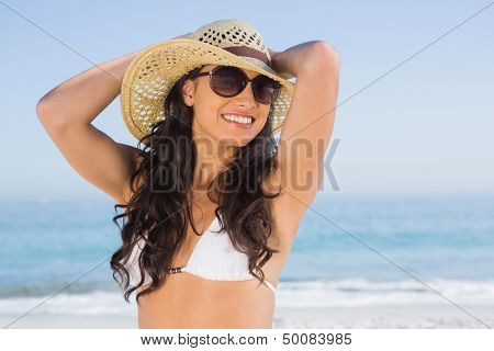 Cheerful attractive brunette with straw hat and sunglasses on the beach
