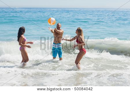 Cheerful friends playing with a beachball in the sea together