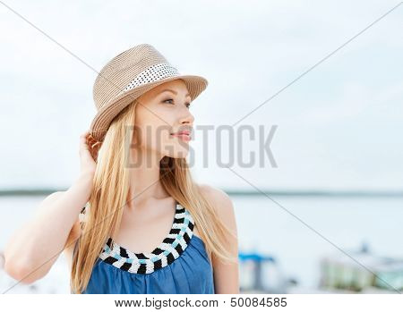 summer holidays and vacation concept - girl in hat standing on the beach