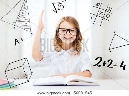 education and school concept - little student girl studying and raising hand at school