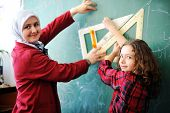 Cute lovely Arabic school children at classroom having education activities poster