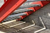 Red metal stairs and shadows on concrete poster