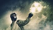 Man in respirator against nuclear background touching symbol. Pollution concept poster