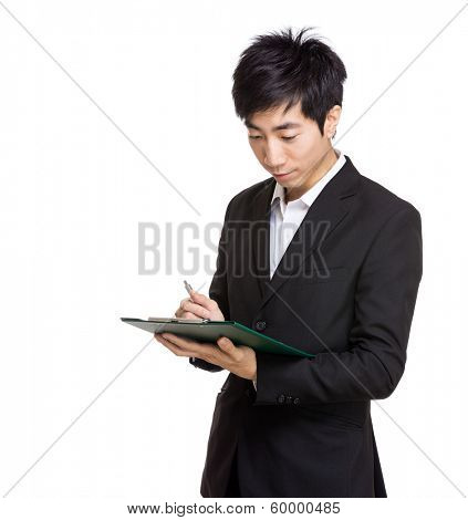 Asia businessman writing on file pad