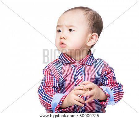 Asian baby holding toy block and looking aside