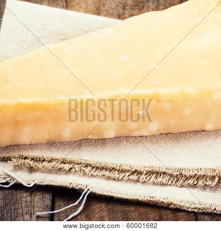 Parmesan Cheese On Wooden Background Close Up. Piece Of Parmesan Cheese On A Napkin, Studio Shot.