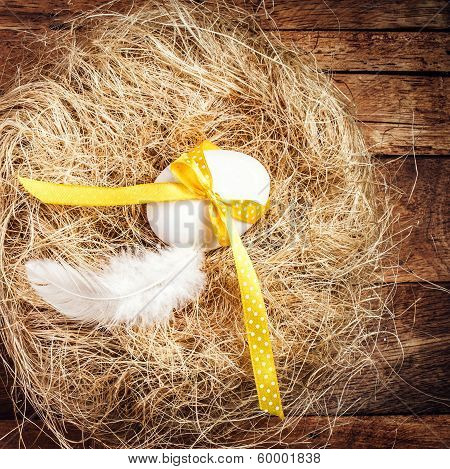 Easter Nest With Egg, Yellow Ribbon And White Feather On Wooden Background With Copyspace For Text I