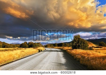 The huge cloud lit yellow-orange rays of sunset. Gravel road through the Patagonian steppe