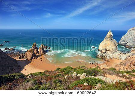 Portuguese Atlantic coast. Bizarre sandstone rock on the small beach in Sintra. Several tourists were roasting in the sun