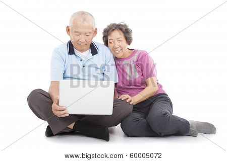 Happy Senior Couple Watching Or Learning With Laptop