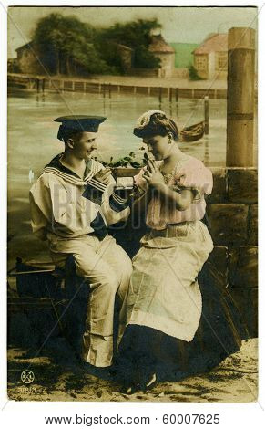 MOSCOW, RUSSIA - CIRCA 1910s: An antique hand painted photo shows studio portrait of sailor and his bride.