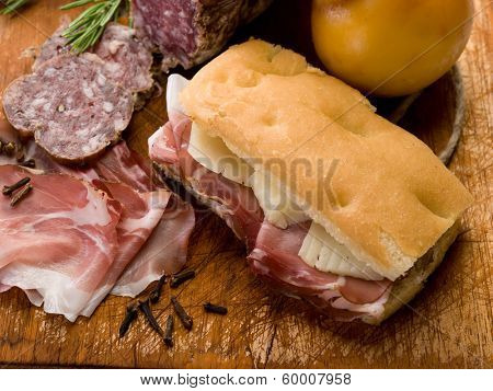 focaccia with ham salami and cheese over cutting board
