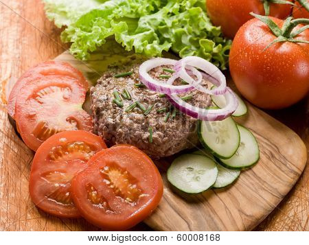 hamburger with slice vegetables over cutting board