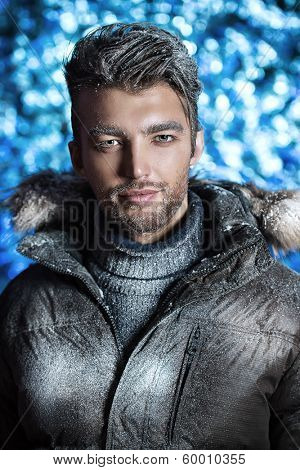 Portrait of a handsome man dressed in winter clothes, covered with snow.