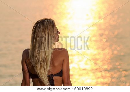 Beautiful Woman In Front Of The Ocean Watching The Sunset
