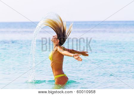 Beautiful Tanned Woman Playing In The Sea