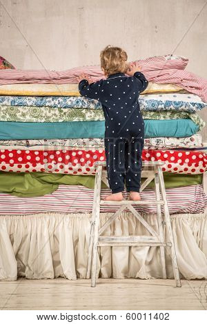 Child climbs on the bed with lots of quilts - Princess and the Pea.