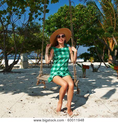 Woman in green dress swinging at tropical beach