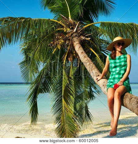 Woman in green dress sitting on a palm tree at tropical beach, Maldives