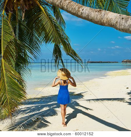 Woman in blue dress on a tropical beach at Maldives