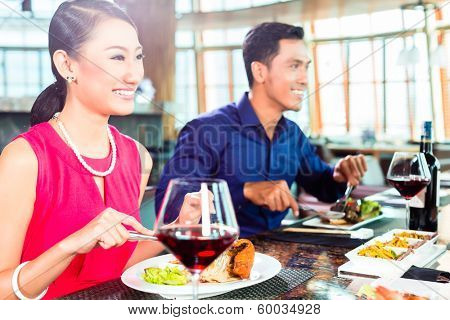 Asian people having dinner and drinking red wine in very fancy restaurant with open kitchen in background