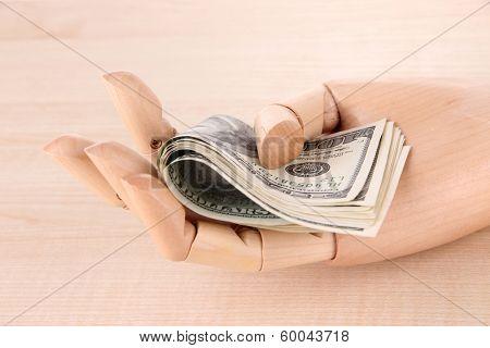 Money in wooden hand, on wooden background