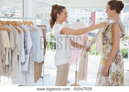 Side view of a saleswoman assisting woman with clothes at the clothing store