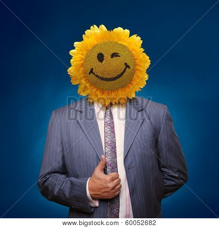 Smiling Sunflower Head Man In Suit Coat With Present Thumbs Up Over Blue