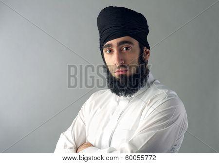 arabian muslim man wearing black head scarf looking at the camera