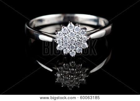 White gold ring with diamonds shot on black surface, macro