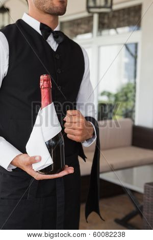Waiter holding magnum of champagne in the patio of restaurant